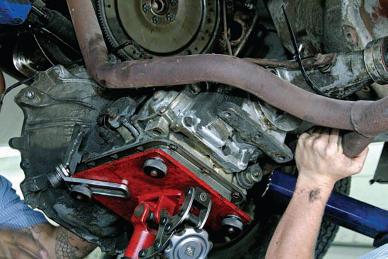 Old transmission removal means being prepared with fluid drainage from both the sump and the torque converter. Disconnect the driveshaft, shift, and kickdown linkages. Have a solid means of support beneath the transmission.