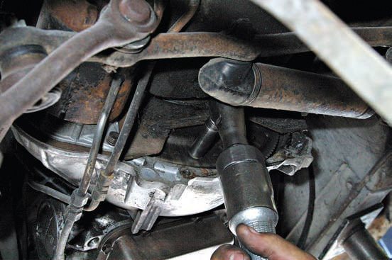 Remove the dust cover to get at the torque converter and flexplate. Remove the torque converter fasteners with a 5/8-inch socket. Rotate the engine crankshaft to get at hard-to-reach fasteners.