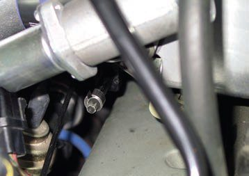 The equivalent of the T86L-70332-A TV cable adjustment gauge fits between the cable adjuster and cable end (arrow). With the cable pulled 25/64 inch (10 mm) and locked at this dimension, you should have 33-psi throttle valve pressure at idle in neutral. Set the adjustment, remove the gauge, and you should have 5 psi. You can make this gauge with a stack of washers glued together to a thickness of 25/64 inch (10 mm).