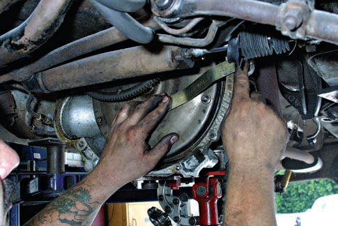 Protect the torque converter during transmission removal. The converter can fall out and cause severe damage to both the converter and your feet. You can use a piece of band iron or even a box-end wrench with a bolt through the bellhousing to keep the converter in place.