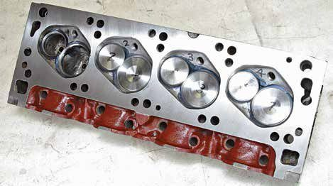 Although this looks like a 351C-4V cylinder head, it is a Boss 302 cylinder head modified to fit a 351C-4V engine. The difference is the cooling passages (arrows) bored into the casting of a 351C engine. This cylinder head was removed from a 351C-4V engine during a rebuild. The builder, MCE Engines, was surprised to discover its Boss 302 status and the Cleveland cooling passages plugged with epoxy.