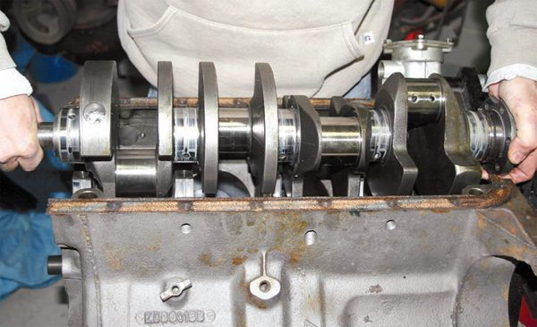 Once the main bearing caps have been removed, you can lift the crankshaft out of the block. V-8 crankshafts are typically 50 pounds or more, so be sure you can lift it out yourself or get someone else to help. If you drop it, you can damage it beyond repair.
