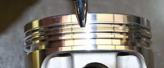 The RaceTec piston in this performance engine build is a thoroughly modern design and features an accumulator groove, which, by design, collects any gases that manage to escape (blow by) past the top piston ring. It also prevents the ring from being disrupted; it is allowed to seal properly against the cylinder walls.