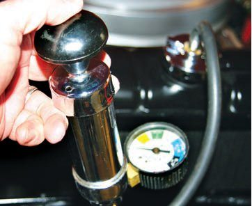 Use a cooling system pressure tester to detect cooling system leaks; it is a good way to reveal leaking or blown head gaskets. Fit the pressure tester in place of the radiator cap, and apply pressure to the cooling system by squeezing the bulb attached to the device. With the cooling system pressurized, look for fluid leaks around the cylinder heads or any drops in pressure (as indicated on the gauge) that are indications of existing problems. If you remove the oil filler cap while conducting a cooling system pressure test you will hear air leaking internally. A hissing or gurgling sound that emanates from the oil filler neck once the cooling system has been pressurized is a strong indication of an internal leak.