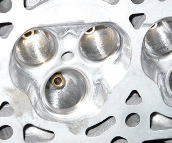 The SOHC threevalve head has unique cross-flow chambers that offer generous intake flow with improved exhaust scavenging. The recessed spark plug is positioned mid-chamber. This CNC-ported and hand-polished three-valve head from PowerHeads yields dramatic high-RPM performance improvements.