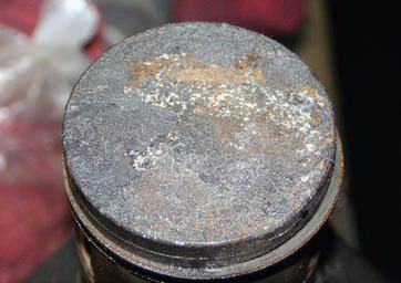 Pistons can be read to determine what has been happening in individual cylinders in an engine when it was running. The top of this piston shows an accumulation of carbon buildup that is indicative of the engine's mileage. If I had observed pitting on the top of the piston, it would have been a sign of detonation because of an overly lean fuel mixture or incorrect ignition timing.