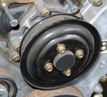 Front dress depends on vehicle application. As a rule, the basics don't change much, which includes a spring-loaded tensioner for the serpentine belt-drive system and idler pulleys to take up the slack. The Mustang's water pump pulley has a lip to prevent belt derailment. Not all water pump pulleys have this lip.
