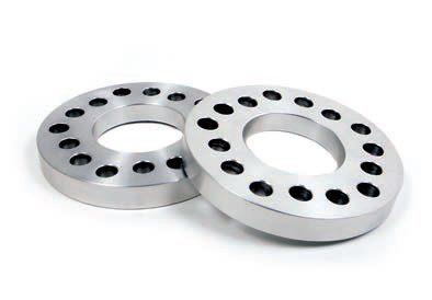 New discs may have differences in hub thickness and/or other components (steering knuckles, for example), which result in the hub surface moving. Similarly, larger brake calipers may require wheels with a different offset, which may also move the tire laterally. One way to restore the correct location is through the use of wheel spacers such as these made by Baer. They're usually available in thicknesses from about 1/4 to 1 inch with various bolt patterns. (Photo Courtesy Baer Racing)