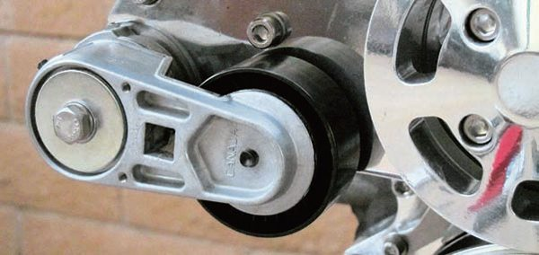 The belt tensioner is almost the last component to go on. It has two small pegs on its rear face, which go into two corresponding holes on the front support plate for proper alignment. Use the single bolt to keep everything tied together.