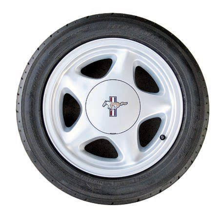 If you want to introduce the style of a later-model Mustang to your project there are many possibilities. This is a 16-inch 5 Star/Pony wheel from a Fox-Body. These are available with the proper five-lug bolt pattern (the Fox originally used a four-lug pattern) and offset for the early cars. The upgrade to 16 inches not only changes the look of the car but can also allow for slightly wider tires. The larger diameter reduces potential interference with the front ball joints, thus allowing the wheel to tuck in more. They are easy to find in a 7- or 8-inch width plus many other sizes, diameters, and offsets. Alternative finishes such as chrome, black, or even white are also offered, though with fewer size options. The jump to 16 inches also allows many larger disc brake packages to be used. Tire widths of 225 front and 245 rear should fit a 19641 ⁄2–1966 with no problem on 8-inch rims with a 4.5-inch backspacing. Later cars can go considerably larger in width and diameter. A package such as this is ideal for relatively comfortable street use and can also be used in autocross, open road, drag strip, and brief track events with little risk.