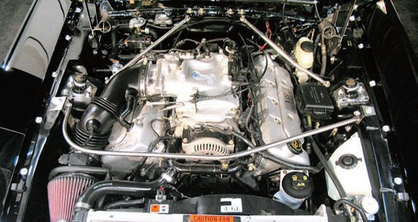 The installation of a modular engine in these Mustangs requires extensive modification to the engine compartment for it to fit. This is due primarily to its significantly greater width than the older pushrod engines. The two-valve version (shown) is not as tight a fit but even it usually requires removal of the shock towers (shown) along with the installation of a completely different suspension system. The twovalve/SOHC modular engine can fit in the 1967 and later cars more easily because they originally had big-blocks available as an option. It's much more difficult to put one in an earlier Mustang and really is not practical except for a special show car.