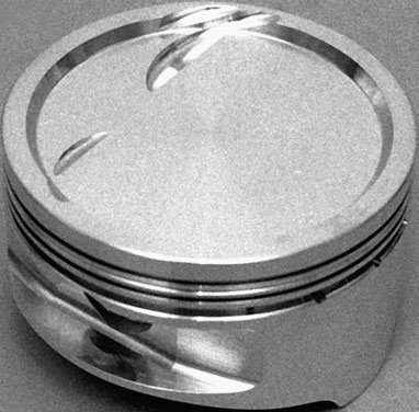 The piston's design is a huge factor in both compression and clearance volume at top dead center. Here's a dished piston. We have to figure in clearance volume on both the dish and the valve reliefs. A dished piston increases clearance volume, which decreases compression ratio.