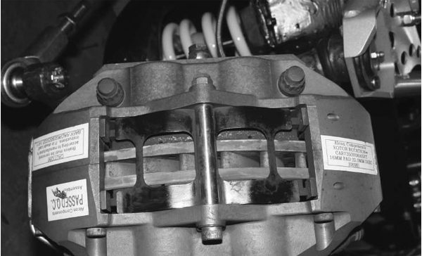 This is a mono-block Alcon caliper with staggered bores. The piston bores are staggered in size for better pad wear. The term mono-block means that the caliper is machined from a single-cast unit, which makes it extremely rigid. The design eliminates the need for an external balance tube.