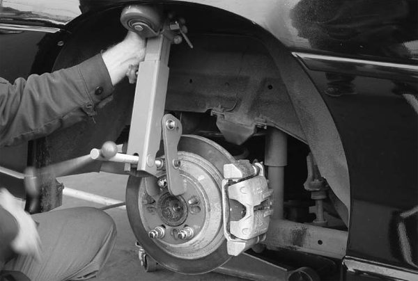 This fender-lip-rolling tool is the best thing since Star Wars. It's bolted to the axle, adjusted to the lip of the quarter, rolled back and forth, and then adjusted more. This process is simpler and cleaner than using a baseball bat.