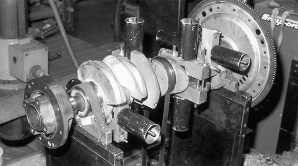 When all of the components have been machined, they are dynamic balanced as shown. Dynamic balancing weighs each piston and rod assembly, and gets all of them weighed to the lightest unit in the set. The crankshaft is spun as shown to determine counterweight mass. Each counterweight is drilled to remove weight, getting the weight down to that of the lightest counterweight, matched to the lightest piston and rod assembly.
