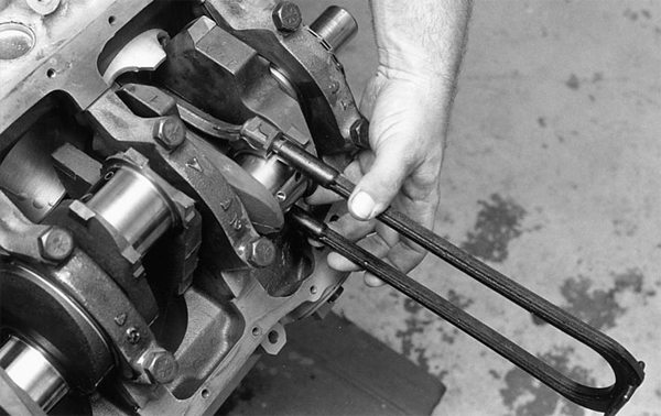 """Protect cylinder walls and crankshaft journals from nicks and scores by covering the rod bolts as shown. Rod bolts are made a much harder metal than cylinder walls and crankshafts. Just a gentle tap will damage the surface. Cover the rod bolts. You may also use plastic caps, called """"rod bolt condoms"""" to protect tender surfaces. If these are unavailable, use fuel hose of the appropriate size."""