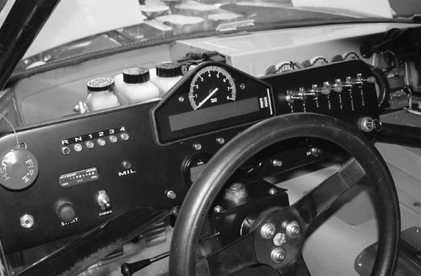 This racing dash is all business. It houses all the accessory switches, fire system activation knob, and a Stack gauge that has an analog tach. Under the tach, there's digital readout that shows multiple gauge functions. It's an all-in-one unit.