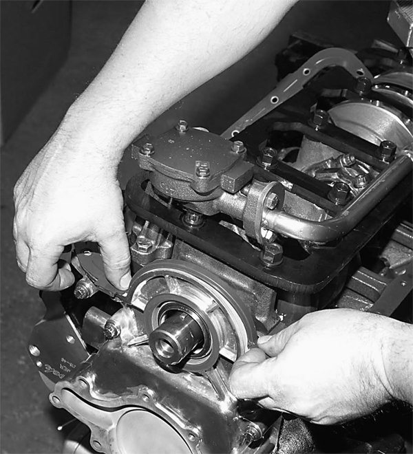 Above and right: Late-model 5.0L blocks use a one-piece oil pan gasket that is easy to install and remove. Enthusiasts like the one-piece, no-leak design. John lays this revolutionary gasket in place, checks fit, and installs the Canton pan. Bolts are tightened in a crisscross fashion, which secures the gasket and the pan.