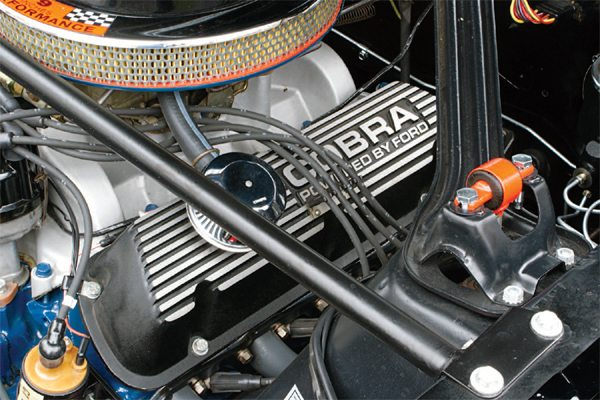 "The ""aluminization"" of the 1966 GT350 engine is basically the same as in the 1965 cars (cast-aluminum intake manifold, cast-aluminum deep sump COBRA oil pan, and cast-aluminum COBRA valve covers). There was a change made, in the interest of cost economics, to the valve covers. Early cars continued to use the bare aluminum, sand-cast Buddy Bar valve covers (left), but later 1966 cars used a die-cast valve cover done in a black wrinkle finish (right)."