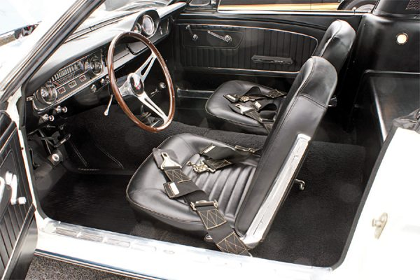 Just as the 1965 GT350 could be had in any exterior color as long as it was white, the same went for black and the interior. Standard Mustang vinyl seats and door panels gave a basic, no frills and very businesslike atmosphere to the cockpit; it was a couple years before Shelbys got deluxe interiors. Additional engine instrumentation in the form of an oil pressure gauge and tachometer were encased within a plastic pod that Shelby American called a bezel and mounted on the dash pad. A real wood steering wheel and 3-inch racing-type seat belts finished off the driver's office.