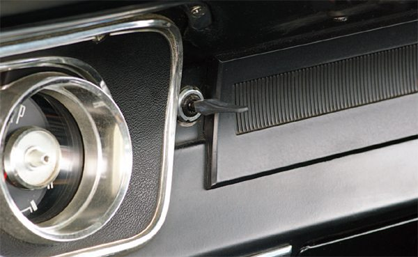 Nestled between the edge of the dash bezel and the radio blockoff plate (real sports cars don't have radios) is the paddlebladed toggle switch activated the horn. Shelby American sought to integrate a horn switch in a wood steering wheel for 1966; it received a horn but had to settle for simulated wood.