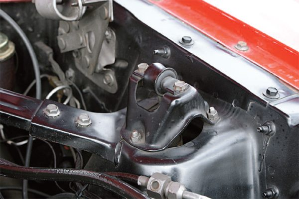 The engine compartment of the stock Mustang was stiffened by stamped-steel braces that triangulated the firewall and the shock absorber towers. These braces were bolted to a flange at the firewall (left) and bolted to stub ends that were welded to the shock tower (right); in all, the parts count was four, with two weld-ons and two bolt-ons.