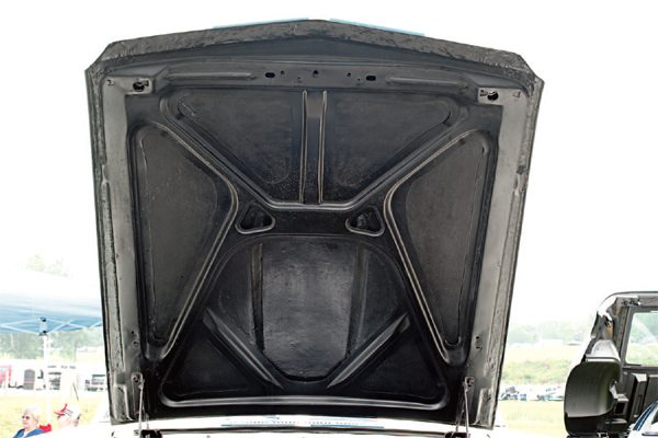 """Early 1965 GT350 hoods were all fiberglass and featured a screened-over circular opening under the scoop, giving the hoods the nickname of """"portholes"""" (left). A later revision of the all-fiberglass bonnet featured a large opening in the underside that was the same size and shape as the scoop itself. Problems with the hood warping when closed persisted and were rectified by the deletion of the hood springs and the incorporation of a steel frame. Mustang hood frames were supplied to Cal Automotive, which fabricated most, if not all, of the fiberglass engine covers, where they were bonded to fiberglass upper hood skins to create the final version of the 1965 GT350 hood (right)."""