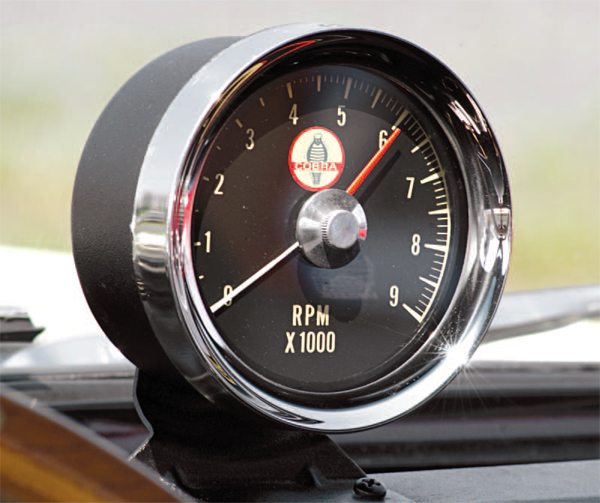 "Perching the tachometer atop the dash pad was the simple solution to a complicated problem: Shelby American had wanted to utilize the molded pod that integrated the tachometer into the Mustang's padded dash—à la the 1965 GT350—but that pod was designed to incorporate not only the tach, but also an oil pressure gauge and the 1966 GT350 instrument cluster already had an integral oil gauge. It would have been possible to retool the pod to incorporate only the tach, but the 1966 GT350s were going to be built from a mix of both 1965 and 1966 Mustangs, and the dash pads were different between the two years. Utilizing the ""tach in a pod"" concept would therefore entail having to develop tooling for two different pods, and this was felt to be too costly. A single bracket mounted the tach atop the dash pad, so swapping a ""tach in a pod"" for a ""tach in a can"" solved the problem nicely, and saved Shelby a tad more than twenty bucks per car in the process."