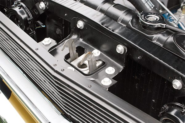 Early 1966 cars with deleted hood latches used a lower-cost means than in 1965 to support the grilles in 1965: a large triangular stamped support. But in early 1966 it went to two simple flat straps (left). Later 1966 cars went even further in the cost reduction department and simply left the Ford hood latch on the cars (right).