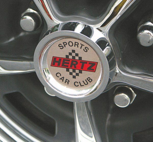 Both the GT350H and GT350 wheels used the same chrome-plated plastic center cap and chrome lug nuts. The Hertz cap got a special gold foil HERTZ SPORTS CAR CLUB, while production cars sported the familiar red, white, and blue Cobra logo in the center.