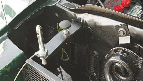 "As on the 1965 and 1966 Shelby, the welded-on hood bumper supports on the radiator support were used to mount the hood pin studs, but the longer hood of the 1967 Shelby meant that extensions were required to position the studs farther forward. Later cars with two-piece grilles had the hood pin lanyards riveted to these extensions, while earlier cars with single-piece grilles secured the lanyards to the grille mesh. The ""D"" grease penciled on the radiator support is part of the designation ""K/D,"" which stood for ""knocked down."" All Mustangs bound for Shelby American were so marked to let Ford quality inspectors know that these cars were supposed to be shipped missing all those body parts."