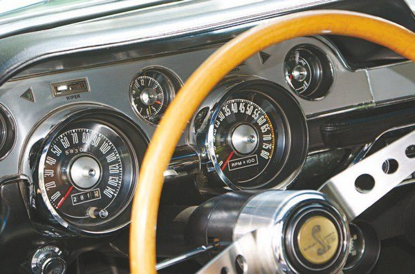 "As in 1966, Ford offered a deluxe interior in the Mustang but unlike before (where the instrumentation remained but the dash bezel trim changed), the deluxe dash contained different instruments. The standard dash incorporated a split oil pressure gauge (above) and ammeter (below) in the right large circular gauge. Finish was camera case black plastic and chrome and the small center gauge was a dummy. The deluxe interior fit a tachometer into the large right gauge and oil pressure and ammeter changed to ""idiot lights"" on the tach face. Trim was brushed aluminum and chrome and a clock sat in the center opening. Wanting both the tach and the gauges, the choices were the standard dash with an add-on tachometer or the deluxe interior with add-on gauges; Shelby chose the latter. By 1967, the radio had become standard in the Shelby"
