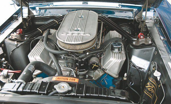 "The biggest complaint of the earlier Mustangs (and hence, Shelbys) was the lack of room between the shock towers for a big-block engine. The 1967 Mustang remedied that (although there still wasn't a lot of room). Hydraulic-liftered Police Interceptor 428 (unique to the Shelby GT500, the Mustang GT receiving ""only"" a 390) was topped with dual 600-cfm Holleys on an aluminum intake (a Ford aluminum intake, not a Shelby-unique item). Cast-aluminum valve covers and air cleaner top completed the ""aluminization"" of the GT500 engine room."