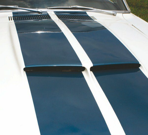 Wide LeMans stripes were never offered from the factory, but many owners added them to what they thought were too-plain 1967 Shelbys. It is just good fortune that the regulation 10/2/10 stripes fit neatly within the opening of the split hood scoop.