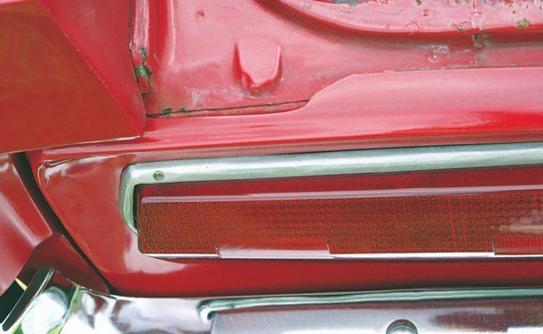 A second iteration of tail panel carried a lip up and over onto the crosswise rail of the trunk opening rear. The lack of attaching screws into this lip suggests its primary purpose might have been to provide a shield for the seam between the tail panel and the rear face of the car to prevent water intrusion into the trunk. A fix for poor-fitting fiberglass of this variant was a series of rivets run into the back of the tail panel from inside the trunk.