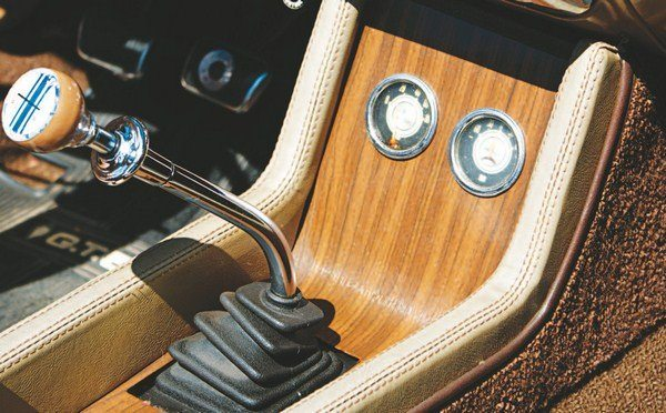 """For the first year ever, the Shelby Mustang received a betweenthe-seats floor console. Similar to the Mustang unit, the Shelby console replaces the sliding """"garage door"""" storage compartment with an angled section that houses the ammeter and oil pressure gauges. Like in the 1967 Shelby, the 1968 dials are also furnished by Stewart-Warner. Mounted in the wood-grained floor console, they have a somewhat more integrated appearance than 1967's upside down Rally-Pac housing. Two pull knobs to the left of the console controlled the driving lights and (on convertibles) the power top."""