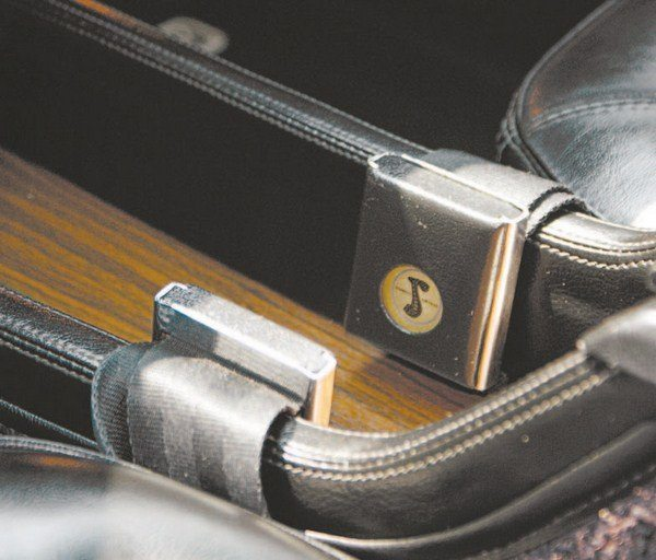 The center section of the floor console features clips to stow the front seat belts when not in use.
