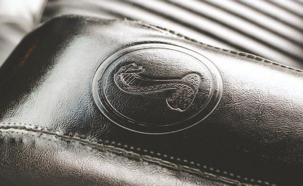 A unique armrest was used on the Shelby floor console (left) that contained an embossed Shelby logo (right).