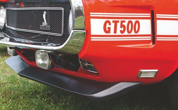 """In order to create the impression that the 1970 Shelbys were somehow different from the 1969 models (which they really weren't, and, in fact, were unsold 1969 models renumbered with 1970 VIN numbers), two black hood stripes were added to the hoods of the """"new"""" 1970 cars (left). A plastic Boss 302-like spoiler (right) was added to the chin to further differentiate the two years' models. Although very close in appearance to the chin spoiler of the Boss 302 and 429 Mustangs, the Shelby piece was in fact different, necessitated by the different contours of the Shelby lower front valance."""