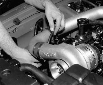 15. The idle air control valve is joined to the 4.6L throttle body housing reusing the original factory hose. It is then re-routed to the air discharge tube via the supplied length of rubber hose and hose clamps provided in the kit.