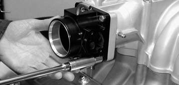 30. Heading into the home stretch, we see Central Coast Mustang's black anodized variable-venturi 65- to 75-mm throttle body being installed using a series of four 5⁄16-inch bolts.