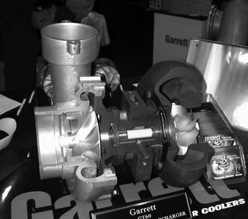 The Garrett GT40 turbocharger is factoryrated for engines displacing 3.5L to 5.0L. This turbo is ideal for both V-6 and V-8 small-block Ford applications operating within the 370 to 650 hp range. This cutaway clearly shows theGT40's key components including the compressor housing and compressor wheel (right), turbine housing and turbine wheel (left), and the bearing housing and main shaft (center).
