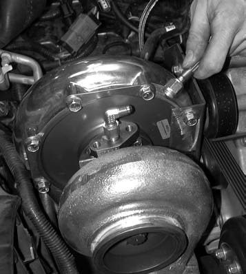 5. Next, a 1⁄2-inch wrench is used to hook up the oil pressure feed line to the 90- degree AN fitting at the top of the turbo housing.
