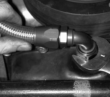 9. A 1-inch wrench is used to tighten the 3⁄8- inch AN fitting that is being installed into the oil pan. Then the oil return line is attached to the fitting.