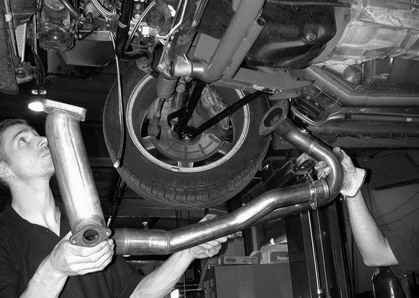 10. Here we see our installers laying up the main turbo inlet pipe. The one side is bolted to the stock passenger-side exhaust manifold, while the other end is bolted to the turbocharger.