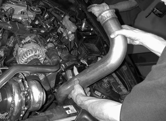 17. The 3-inch turbocharger down pipe, running from the top of the engine compartment, is secured in place with a 3-inch stainless- steel band clamp.