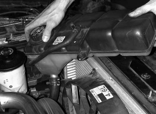 18. The radiator coolant overflow reservoir, which had been temporarily set aside, is reinstalled.