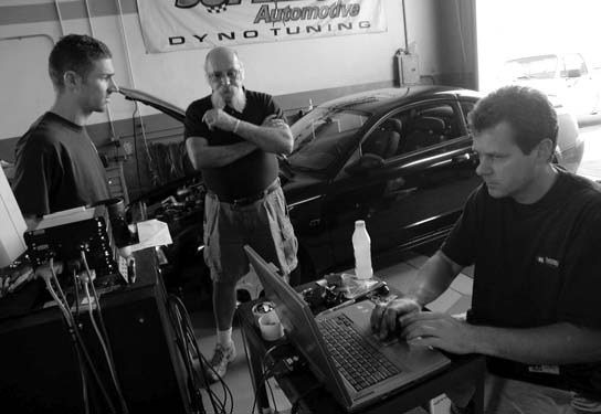 40. With the Hellion Power Systems turbo kit fully installed, it's off to the dyno shop. Here we see Super Automotive's Shawn Ellis burning the first Diablo computer chip as John Urist (left) and Darryl Bassani (center) look on.