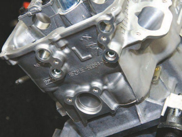 """With the left-hand cylinder head in place, identified with an """"L,"""" it's challenging to see where the head ends and the block begins. The Coyote is a well-thought-out package, where block and head become one. The objective was to come up with a lighter, smaller cylinder head to get unnecessary weight out of the Mustang while conceiving a more swappable engine that can fit more applications. This is how you design and produce a factory high-performance engine."""