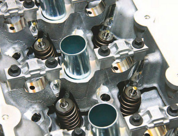 A closer look at the Coyote cylinder head demonstrates the petite nature of this redesigned Modular head with its smaller valvetrain. It reminds me of a motorcycle valvetrain because it is so small. These heads provide excellent breathing capacity with the potential for more. Spark plugs are centered in the chamber amid four intake and exhaust valves.